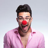 Fashion young man shouts with a red nose — Stock Photo