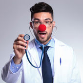 Young doctor listens to you at stethoscope with red nose — Stock Photo