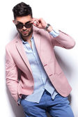 Casual man with hand in pocket takes off sunglasses — Stok fotoğraf