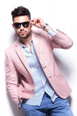 Casual man fixing his sunglasses with a hand in pocket — Stock Photo