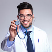 Young doctor with stethoscope smiles — Stock Photo