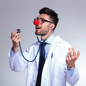 Young doctor with red nose singing in the stethoscope — Stock Photo