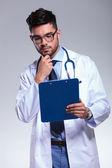 молодой врач смотрит на буфер обмена беспокоился — Стоковое фото