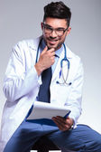 Seated young doctor with hand at chin — Stock Photo