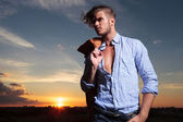 Casual man with sunset behind looks away — Stock Photo