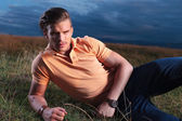 Casual man looks frowned at you, while laying in grass — Stock Photo