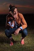 Accovacciato casual uomo ridendo all'aperto — Foto Stock