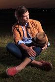 Przypadkowy mężczyzna z kapelusz na kolana wygląda od — Zdjęcie stockowe