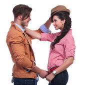 Casual couple with man taking woman's hat off — Stok fotoğraf