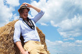 Casual man outdoor on haystack looking at you — Stock Photo