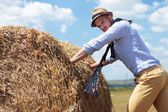 Casual man outdoor pushing a big round haystack — Stok fotoğraf