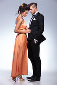 Fashion couple with woman unbuttoning man's jacket — Stock Photo