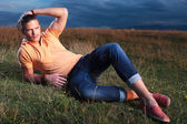 Casual man laying in the grass and fixing his hair — Stock Photo