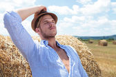 Casual man outdoor leaning back on haystack — ストック写真