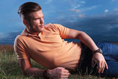 Casual man looks away while in grass — Stock Photo