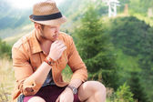 Seated casual man holds a straw in his mouth, outdoor — Stock Photo