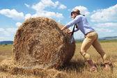 Casual man outdoor pushing a haystack — Stock Photo