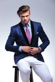 Seated young business man taking his jacket off — Photo