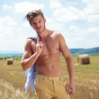 Topless man outdoor on a cereal field with a straw in mouth — Stock Photo
