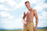 Topless man outdoor looks at you with hand on pants — Stock Photo