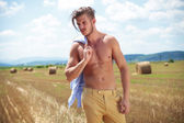 Topless man outdoor with straw in mouth looks away — Stock Photo