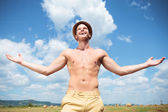 Topless man laughing outdoor with arms wide open — Stock Photo