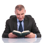 Business man at the desk, reads a book — Stock Photo