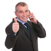 Business man on phone shows thumbs up — Stock Photo