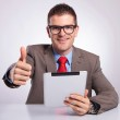 Young business man with tablet shows thumb up gesture — Stock Photo #34370051