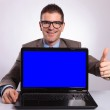 Young business man presents his laptop with thumb up — Stock Photo #34371885