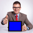 Young business man presents tablet and shows thumb up — Stock Photo #34372057
