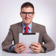 Young business man with tablet smiles for you — Stock Photo