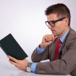 Side of young business man reading a book pensively — Stock Photo #34379333
