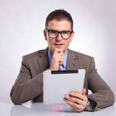 Young business man with tablet holds hand on chin — Stock Photo