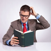 Young business man reads a book and scratches his head — Stock Photo