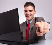 Young business man points at camera while smiling behind laptop — Stock Photo