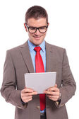 Young business man holds tablet with both hands and reads — Stock Photo