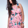 woman in pink floral dress is looking to her side — Stock Photo