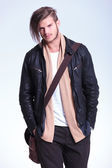 Man in leather jacket is standing with hands in pockets and smil — Stock Photo