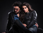 Embraced seated couple in leather jackets — Stock Photo