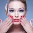 Surprised young beauty woman with fingers on her face — Stock Photo #35160601