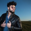 Side view of a fashion man holding his leather jacket — Stock Photo #35161239