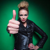 Fashion womanin leather jacket making the ok thumbs up sign — Stock Photo