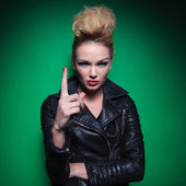 Young fashion woman is pointing her finger up — Stock Photo