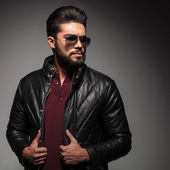 Serious bad boy wearing in jacket and sunglasses looking away — Stock Photo