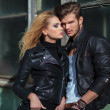 Stock Photo: Couple in leather jackets posing against old building