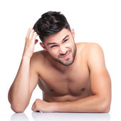 Confused beauty naked man is scratching his head — Stock Photo