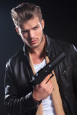 Hitman in leather clothes holding a big gun in his hand — Stock Photo