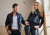 Man in leather jacket is pulling his girlfriend — Стоковое фото