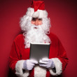 Santa claus is holding and reading on a tablet pad computer — Stock Photo #36080841